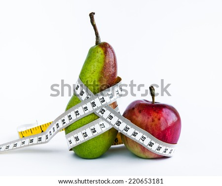 pear and apple wrapped in a measuring tape. Diet. weight loss. wooden background - stock photo