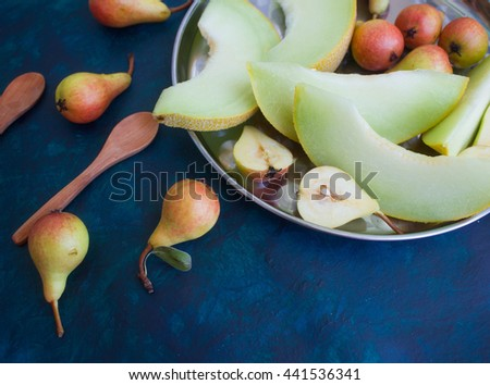 Pear and melon on a dark background - stock photo