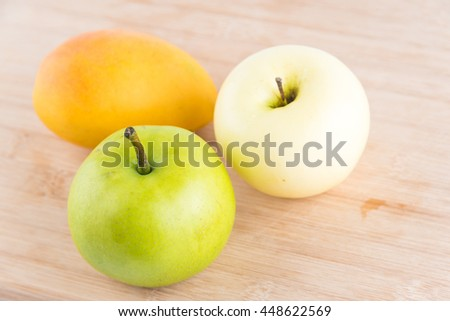 Pear,apple and mango on wooden background