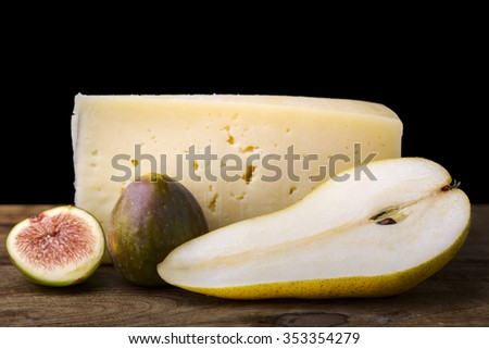 pear, cheese and fig on wood tasty appetizer black background