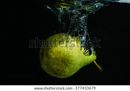 pear falling into water - stock photo