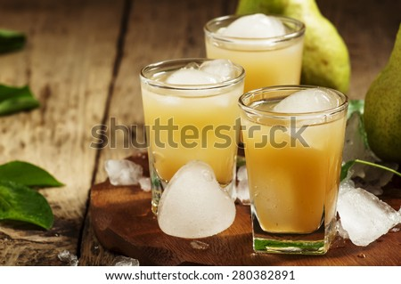 Pear fresh juice with ice in a heart-shaped and pear on a wooden table, selective focus - stock photo
