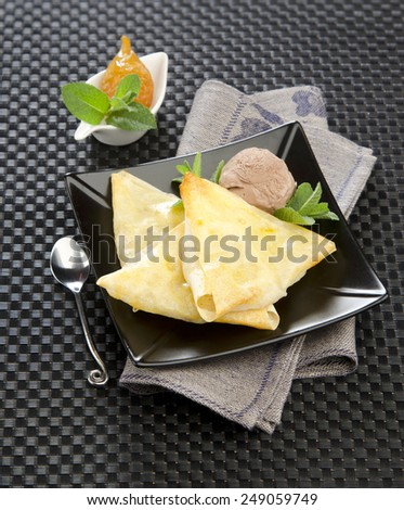 pear in thin dough ice cream with mint on a black plate black background - stock photo