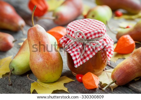 Pear jam and ripe pears on old wooden table. Autumn still life. Selective focus. - stock photo