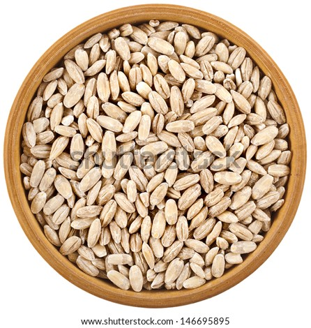 Pearl barley grains heap in bowl top view surface close up isolated on white background  - stock photo