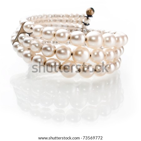 Pearl bracelet of white yellow pearls in three ranks with reflection isolated on a white background - stock photo