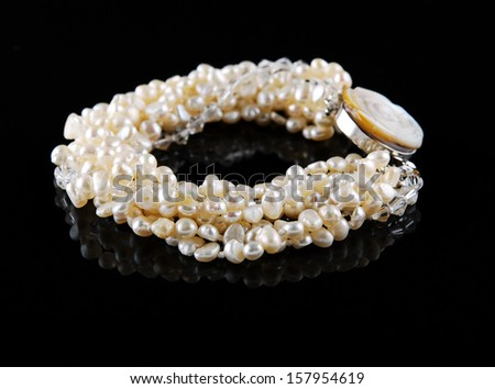 Pearl bracelet on black background - stock photo