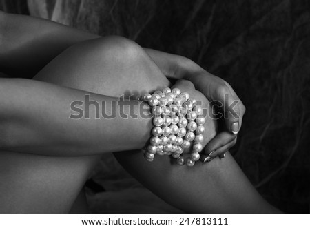 Pearl bracelet on hand in black and white photo, woman hand fragment with pearl bracelet, conceptual photo, jewelry close up, womans hands, body part, jewelry fashion background, fashionable lady - stock photo