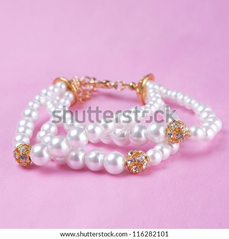 pearl bracelet on pink silk background - stock photo