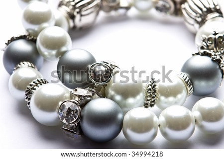 Pearl designer costume jewelery in macro on white background - stock photo