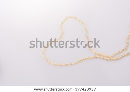 pearl necklace is placed on white background - stock photo
