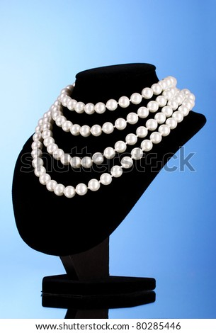 pearl necklace on a mannequin on a blue background - stock photo