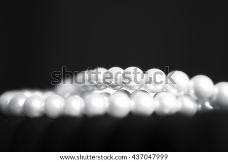 Pearl necklace on black fabric closeup