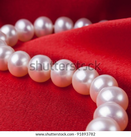 Pearl necklace on luxury satin background - stock photo