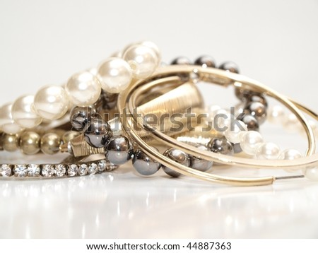 Pearls and ear rings in assorted colors in a pile on white background with reflection - stock photo