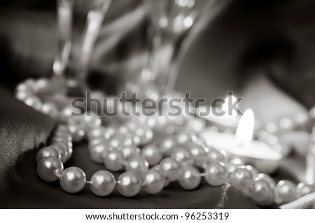 Pearls, wineglass and candles - stock photo