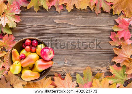 pears  in clay plate with  fallen leaves on wooden table. top view, copy space