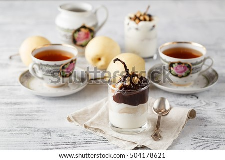 Pears in dark chocolate, sweet dessert set with modern copper colour accessories. Light and contrast photo.