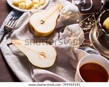 Pears on a napkin on rustic wooden table with wine, honey and cheese