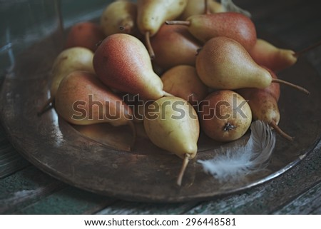 Pears on metal tray on a rustic background - stock photo