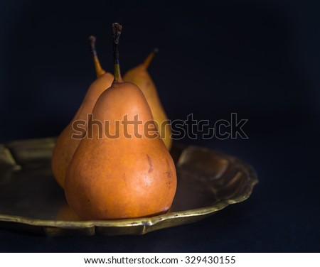 Pears on metal tray on dark background (low-key image) - stock photo