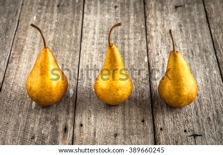 Pears with golden appearance on rustic wooden background - stock photo