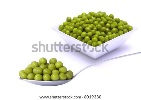 Peas in vegetable dish and on the spoonful - stock photo