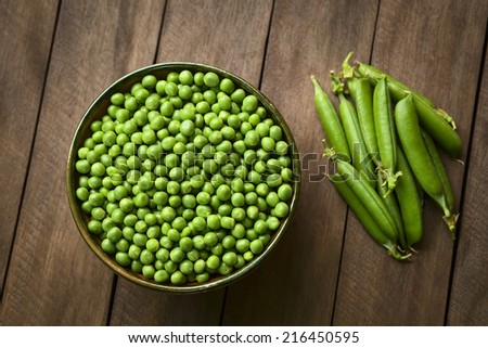 Peas (lat. Pisum sativum) in bowl with closed peapods on the side (Selective Focus, Focus on the lower half of the peas in the bowl) - stock photo