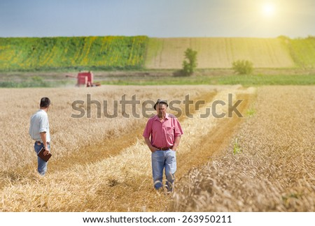 Peasant and businessman standing on wheat field during harvest - stock photo