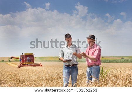 Peasant showing wheat grains to the business partner on the field - stock photo