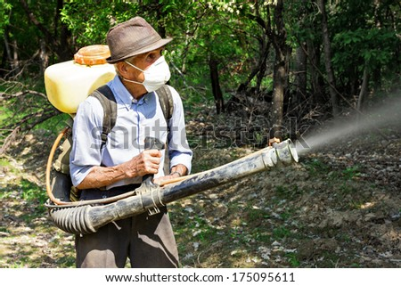 Peasant spraying  trees with chemicals in  orchard - stock photo