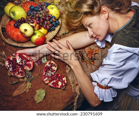 Peasant Woman put her head on the table, where the vegetables and fruits. In her hand cut pomegranate.