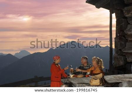 Peasant woman serving couple at alpine hut - stock photo