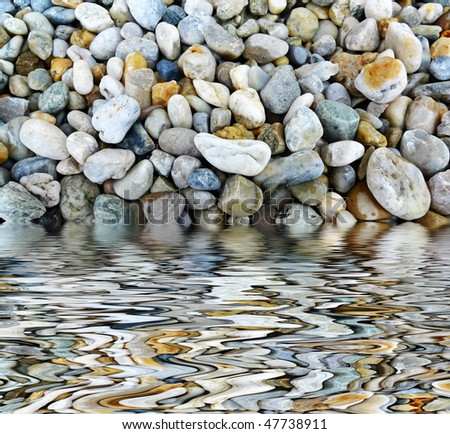pebble and mirroring effect in water - stock photo