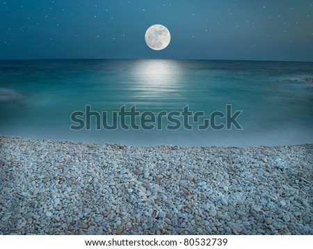 Pebble beach in the the night wit clear sky with stars, lit by the full Moon just above horizon