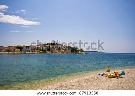 Pebble beach with an easychair and view to Primosten - stock photo