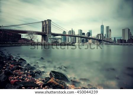 Pebble beach with Brooklyn Bridge and downtown Manhattan skyline in New York City - stock photo