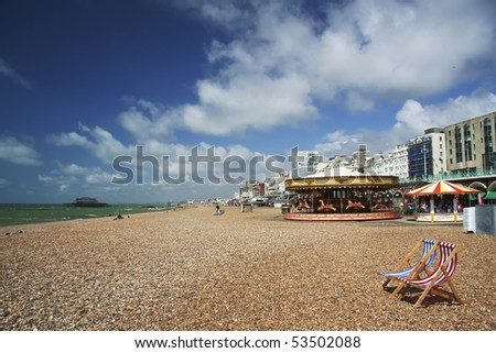 pebble beach with striped red and blue canvas deckchairs, brighton, england - stock photo