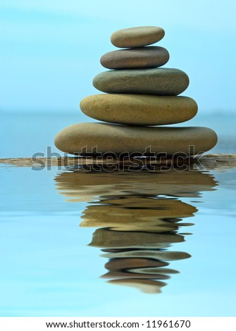 Pebble stack reflecting in the water - stock photo