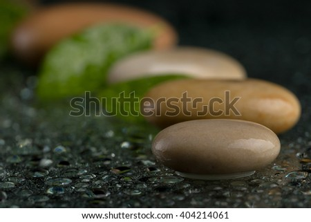 pebble stones and green leaf with water drop, ZEN stone, on black background, spa tranquil scene concept with reflection, backdrop - stock photo