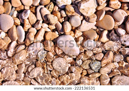 Pebble stones in water on the sun - stock photo