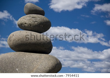 pebbles balanced on each other against a blue sky background - stock photo