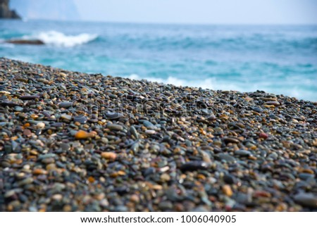Pebbles beach and sea as  background.  Different forms  minerals  as natural abstract texture  multicolor backdrop
