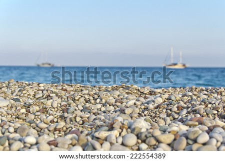 pebbles beach, mediterranean sea, two boats - stock photo