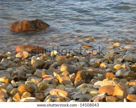 Pebbles in the afternoon light with sea water in background
