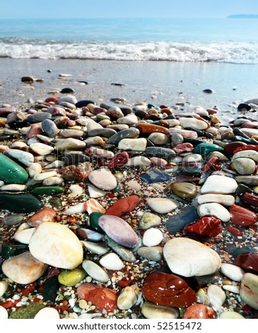 pebbles on the beach and sea background - stock photo