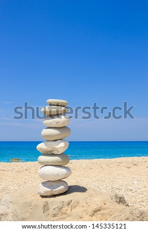 Pebbles stack balance over blue ionian sea in Greece. Blue sky and water on sunny coast in summer. - stock photo