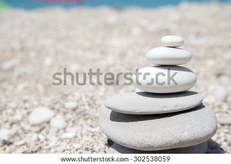 Pebbles stack balance over sandy beach - stock photo