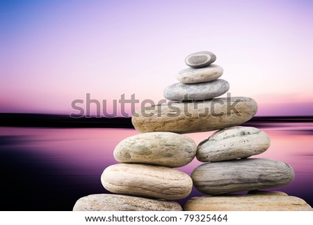 Pebbles stack in peaceful evening with smooth ocean background. Zen concept. - stock photo