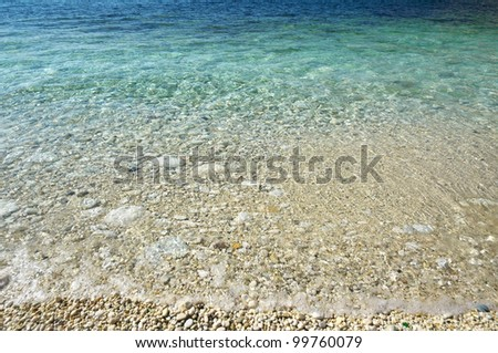 Pebbly beach coastline with turquoise water. - stock photo